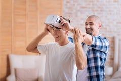 Amis avec plaisir examinant les verres de réalité virtuelle Photographie stock libre de droits