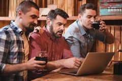 Amis avec plaisir gais regardant l'écran d'ordinateur portable Photos stock