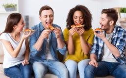 Amis avec plaisir mangeant de la pizza Photo libre de droits