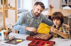 Amis avec plaisir positifs jouant des échecs Photographie stock