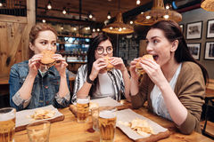 Amis avec plaisir positifs mangeant de la nourriture malsaine Photos libres de droits