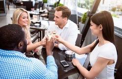 Amis avec plaisir positifs s'asseyant dans le café Photo stock
