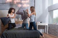 Amis avec plaisir se tenant sur le lit et ayant le combat d'oreiller Photo stock