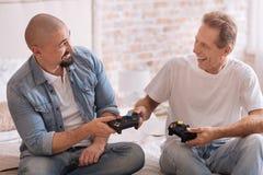 Amis avec plaisir tenant des consoles de jeu dans la chambre à coucher Image libre de droits