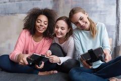 Amis avec plaisir tenant des consoles de jeu et jouant des jeux Photos libres de droits