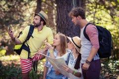 Amis avec une carte regardant une direction Photographie stock