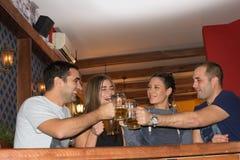 Amis ayant des boissons dans une barre photos stock
