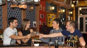 Amis ayant des boissons dans une barre image libre de droits