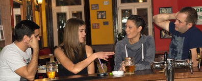 Amis ayant des boissons dans une barre Images stock
