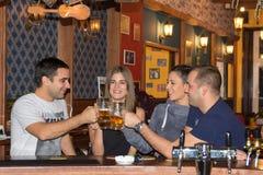 Amis ayant des boissons dans une barre image stock