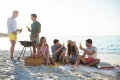 Amis ayant des boissons par le barbecue à la plage contre le ciel Images stock