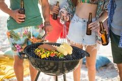 Amis ayant des boissons par le barbecue sur le rivage Image libre de droits