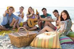 Amis ayant des boissons tout en se reposant à la plage Photos stock