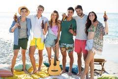 Amis ayant des boissons tout en se tenant à la plage Photos stock