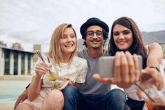 Amis ayant faire la fête sur le dessus de toit Photo stock