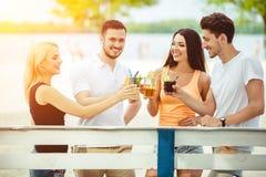 Amis ayant l'amusement à la barre dehors, buvant des cocktails Image libre de droits