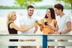 Amis ayant l'amusement à la barre dehors, buvant des cocktails Images libres de droits