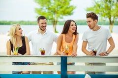 Amis ayant l'amusement à la barre dehors, buvant des cocktails Photographie stock