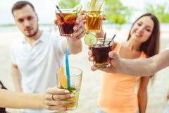 Amis ayant l'amusement à la barre dehors, buvant des cocktails Photos libres de droits