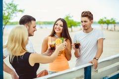 Amis ayant l'amusement à la barre dehors, buvant des cocktails Photos stock