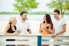 Amis ayant l'amusement à la barre dehors, buvant des cocktails Images stock