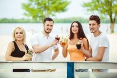 Amis ayant l'amusement à la barre dehors, buvant des cocktails Image stock