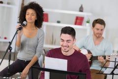 Amis ayant l'amusement à la maison chantant la chanson ensemble Photos stock
