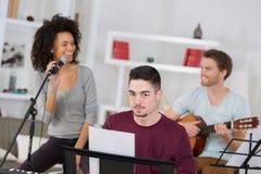 Amis ayant l'amusement à la maison chantant la chanson ensemble Photos libres de droits