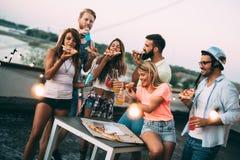Amis ayant l'amusement à la partie de dessus de toit Photographie stock libre de droits