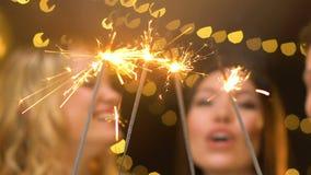 Amis ayant l'amusement à la partie de Noël, tenant des lumières de Bengale et riant, bonheur clips vidéos