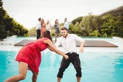 Amis ayant l'amusement à la piscine Photographie stock libre de droits