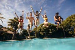 Amis ayant l'amusement à la piscine de station de vacances Photographie stock libre de droits