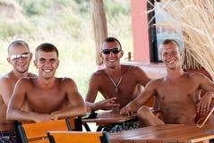Amis ayant l'amusement à la plage en café Image stock