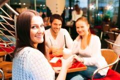 Amis ayant l'amusement à un café Photo stock