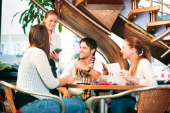 Amis ayant l'amusement à un café Images libres de droits