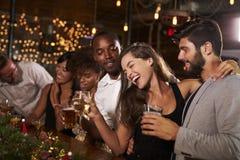 Amis ayant l'amusement à une fête de Noël dans une barre Photo stock