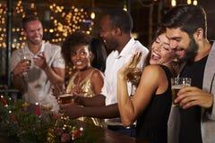 Amis ayant l'amusement à une fête de Noël dans une barre Image stock
