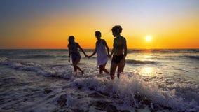 Amis ayant l'amusement éclaboussant des ressacs sur la plage au sunse Images stock
