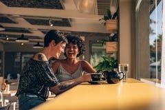 Amis ayant l'amusement au café Image libre de droits