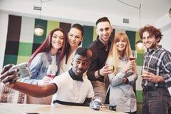 Amis ayant l'amusement au restaurant Deux garçons et quatre filles buvant faisant le selfie, faisant le signe de paix et rire Sur Images stock