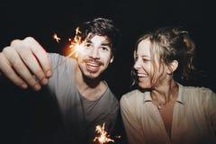 Amis ayant l'amusement avec des cierges magiques pendant la nuit Photographie stock