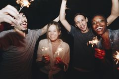 Amis ayant l'amusement avec des cierges magiques pendant la nuit Photo stock