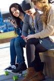Amis ayant l'amusement avec des smartphones Image libre de droits
