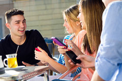 Amis ayant l'amusement avec des smartphones Photo libre de droits