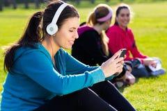Amis ayant l'amusement avec des smartphones après exercice Photo libre de droits
