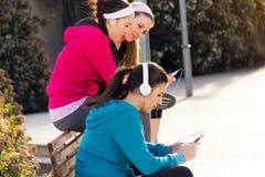 Amis ayant l'amusement avec des smartphones après exercice Photos libres de droits