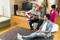 Amis ayant l'amusement avec la guitare Image libre de droits