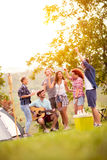 Amis ayant l'amusement avec la musique et les boissons dans le camp Photos stock
