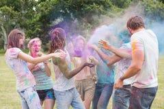 Amis ayant l'amusement avec la peinture de poudre Photos libres de droits