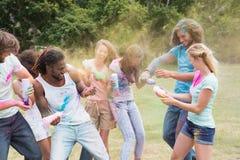 Amis ayant l'amusement avec la peinture de poudre Image libre de droits